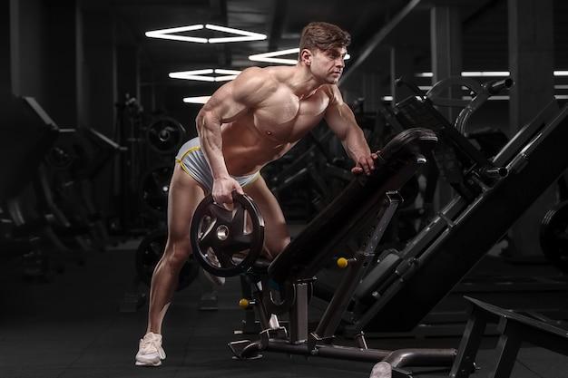 Homem atlético caucasiano exercício bombeamento curvado sobre a linha. fisiculturista forte com tanquinho, abs perfeito. conceito de fitness e esporte
