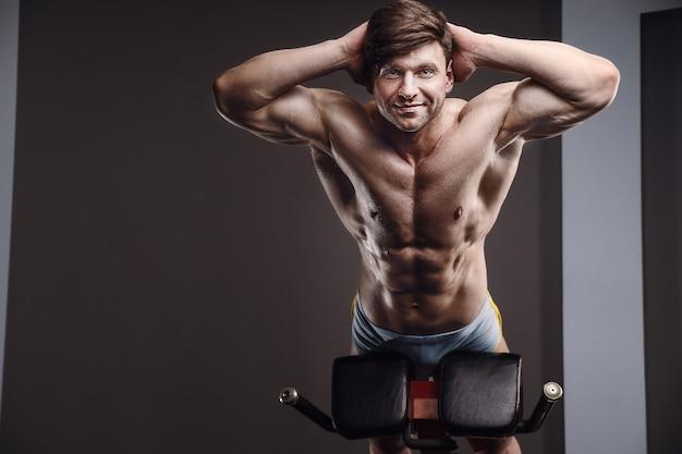 Homem atlético caucasiano exercitando músculos de bombeamento. fisiculturista forte com tanquinho, abs perfeito. conceito de fitness e esporte