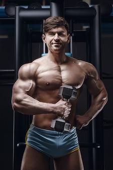 Homem atlético caucasiano exercitando os músculos bíceps de bombeamento. fisiculturista forte com tanquinho, abs perfeito. conceito de fitness e esporte