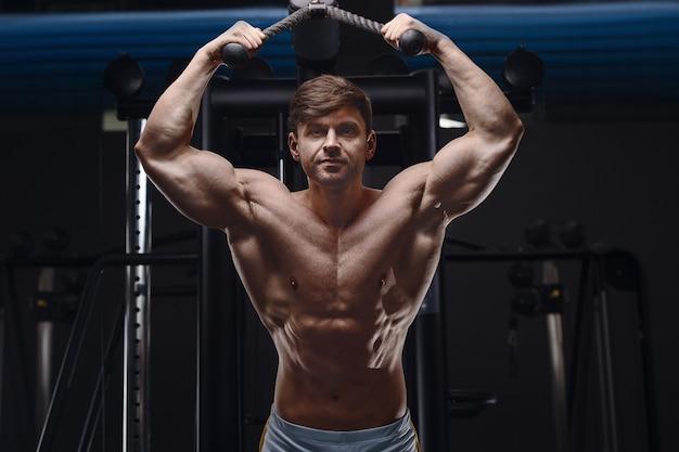 Homem atlético caucasiano, exercitando os músculos tríceps de bombeamento. fisiculturista forte com tanquinho, abs perfeito. conceito de fitness e esporte