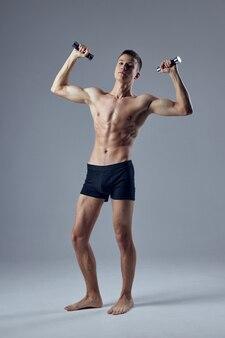 Homem atlético com corpo forte e halteres nas mãos