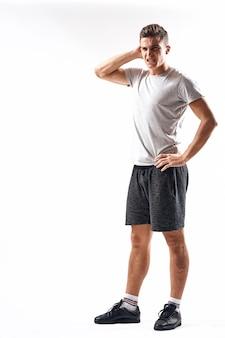 Homem atlético com luz em pleno crescimento e camiseta de tênis de corrida carregando shorts