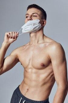 Homem atlético com máscara médica abdominal estimulante, saúde, segurança, treino