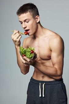 Homem atlético com torso forte e dieta energética com salada