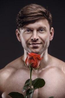 Homem atlético com uma rosa vermelha na mão. conceito de relacionamento amoroso e romântico