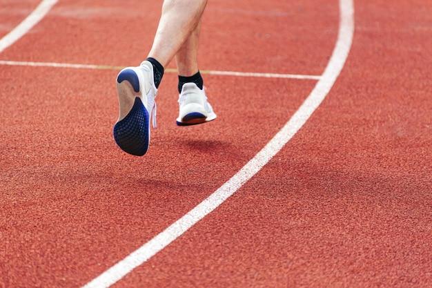 Homem atlético corre e realiza exercícios na quadra do lado de fora. close das pernas de um homem corredor.