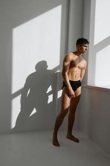 Homem atlético de calcinha preta com corpo inflado olhando pela janela