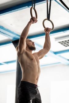 Homem atlético de exercício muscular fazendo exercícios intensos no ginásio em anéis de ginástica