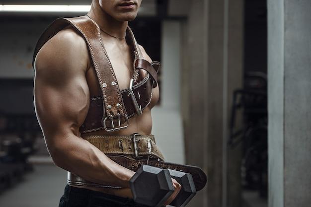 Homem atlético de poder caucasiano treinando músculos bíceps com cinto atlético. fisiculturista forte com tanquinho, abs perfeito, tríceps, peito, ombros na academia. conceito de fitness e musculação