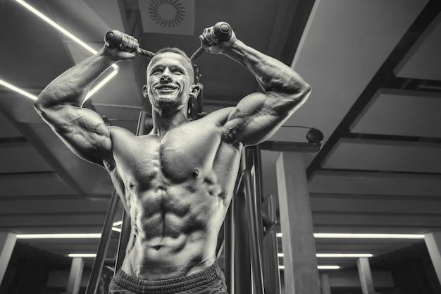 Homem atlético de poder caucasiano treinando para bombear os músculos tríceps. fisiculturista forte com tanquinho, abdômen perfeito, tríceps, peito, ombros na academia.