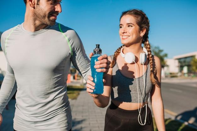 Homem atlético e mulher com bebida azul