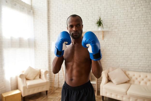 Homem atlético em luvas de boxe está de pé em posição de combate
