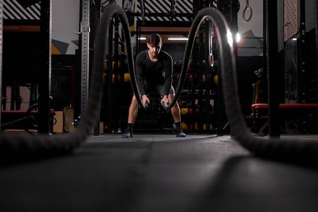 Homem atlético fazendo exercícios de cross fit com corda na academia, concentrado e focado no treinamento, treino. pessoas e esporte, conceito cross fit