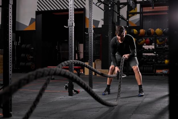 Homem atlético fazendo exercícios de cross fit com corda no ginásio, concentrado e focado no treinamento, treino. pessoas e esporte, conceito cross fit