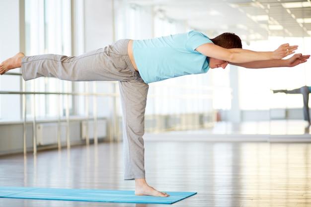 Homem atlético fazendo exercícios de ioga na academia