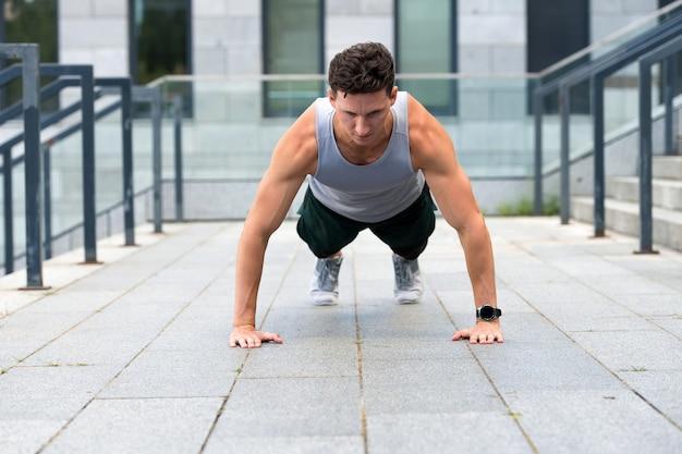 Homem atlético fazendo flexões, conceito de treino urbano.