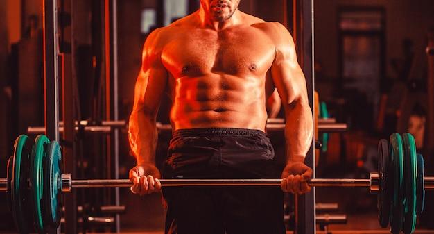 Homem atlético fisiculturista com tanquinho, abdômen perfeito, ombros, bíceps, tríceps, peito. treino de halteres. cara atlético em pé com barra, treino no ginásio.