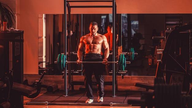 Homem atlético fisiculturista com tanquinho, abdômen perfeito, ombros, bíceps, tríceps, peito. treino de halteres