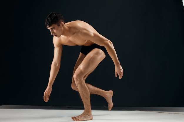 Homem atlético fisiculturista em shorts pretos flexionados joelhos fundo escuro