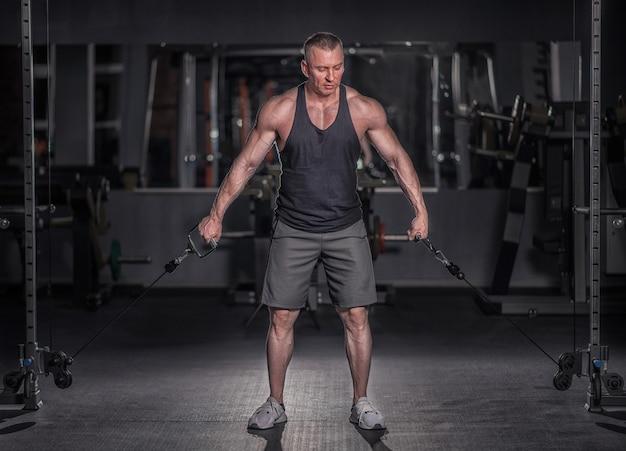 Homem atlético fisiculturista forte brutal bombeando músculos conceito de musculação de treino - homens bonitos de fisiculturista muscular fazendo exercícios no ginásio torso nu