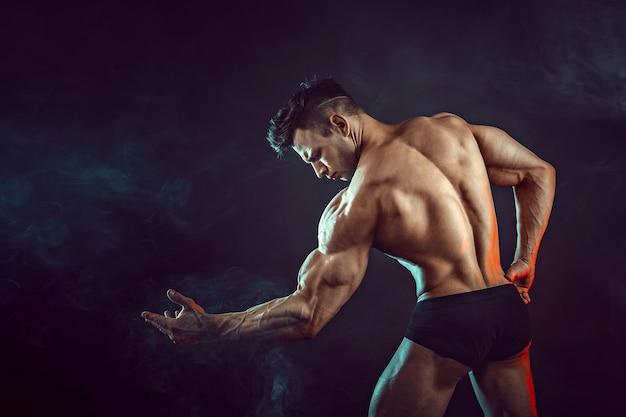 Homem atlético flexionando os músculos com fumaça. fisiculturista forte com abs perfeito.