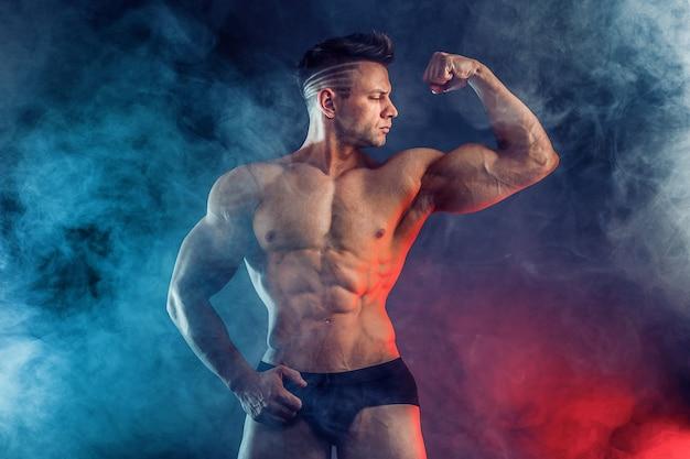 Homem atlético flexionando os músculos em estúdio na parede escura com fumaça. fisiculturista forte com abs perfeito.