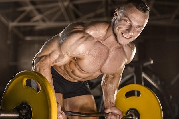 Homem atlético forte, bombeando os músculos das costas