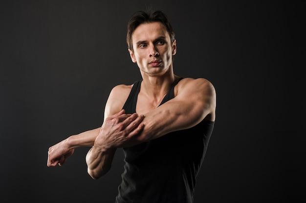 Homem atlético musculoso aquecendo antes de exercitar