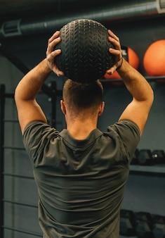 Homem atlético musculoso exercício com bola medicinal no health club ou ginásio