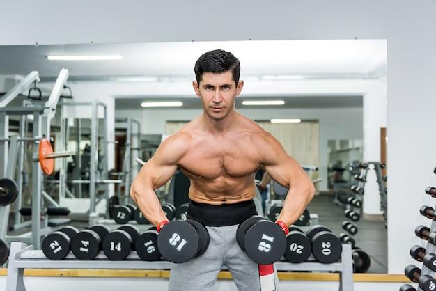 Homem atlético na academia trabalhando com halteres