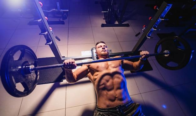 Homem atlético no ginásio exercício no supino barbell.