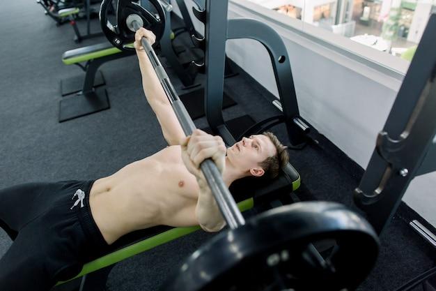 Homem atlético novo que bombeia acima os músculos no supino no gym. jovem fisiculturista treinando na academia: peito - supino inclinado com barra - aderência ampla Foto Premium