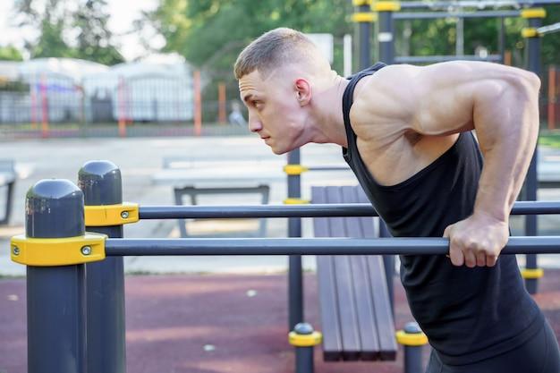 Homem atlético novo que faz push-ups em barras ao ar livre.