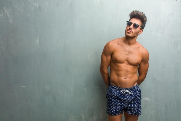 Homem atlético novo que veste um roupa de banho contra uma parede do grunge que duvida e confuso, pensando de uma ideia ou preocupado sobre algo