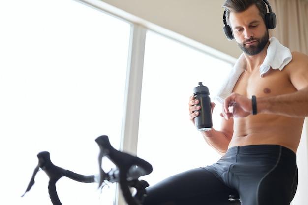 Homem atlético olhando para o smartwatch durante um treino de bicicleta ergométrica