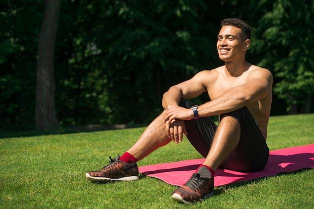 Homem atlético praticando ioga ao ar livre