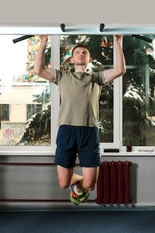 Homem atlético, puxando para cima no ginásio com as pernas cruzadas