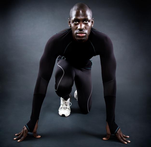 Homem atlético que corre no fundo preto.