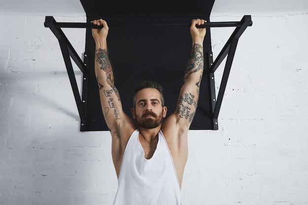 Homem atlético tatuado brutal em camiseta branca sem etiqueta do tanque mostra movimentos calistênicos perto de pullup clássico pendurado na barra de puxar e olhando para a câmera.
