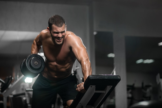 Homem atlético treina com halteres, bombeando seu bíceps