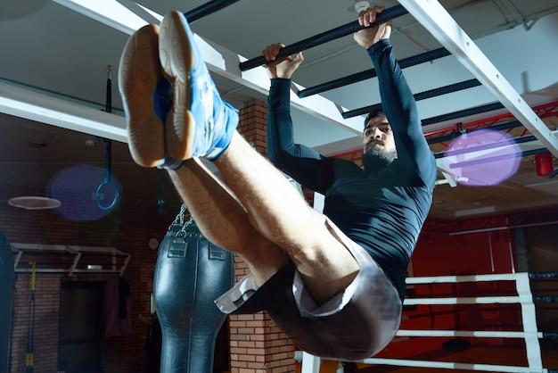 Homem atlético treinamento abs nas barras