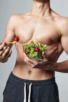 Homem atlético tronco musculoso comida saudável vegetais treino
