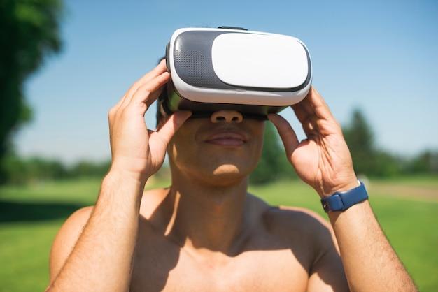 Homem atlético, usando um óculos de realidade virtual ao ar livre