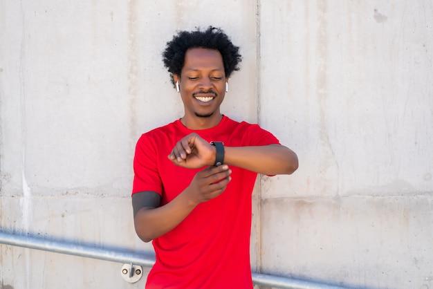 Homem atlético, verificando o tempo em seu relógio inteligente enquanto trabalha ao ar livre. esporte e conceito de estilo de vida saudável.