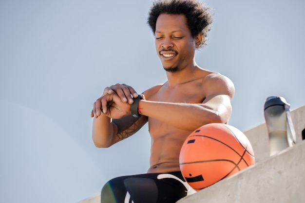 Homem atlético, verificando o tempo em seu relógio inteligente enquanto trabalha ao ar livre.