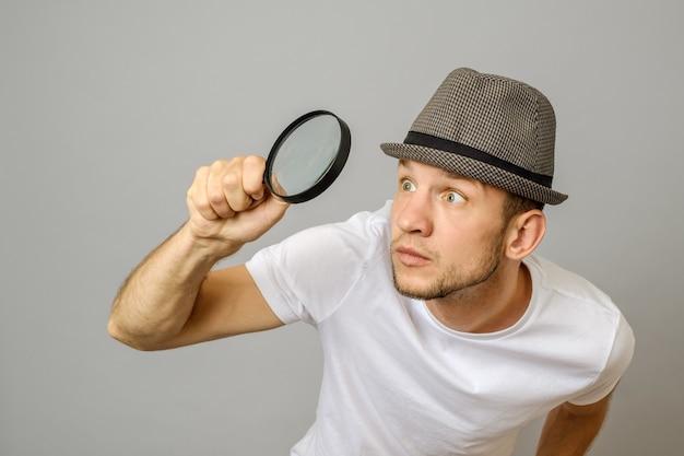 Homem atônito, olhando através de uma lupa