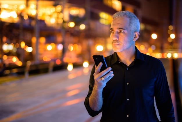Homem atraente à noite nas ruas com as luzes da cidade
