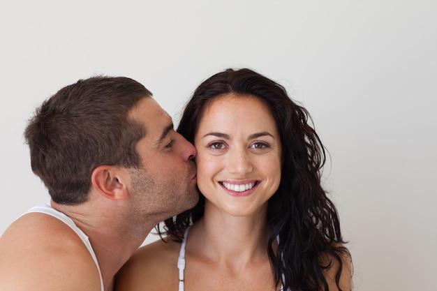 Homem atraente beijando sua namorada sorridente