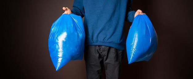 Homem atraente carregando dois sacos de lixo isolados f