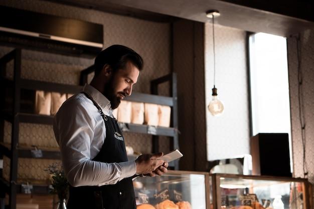 Homem atraente com avental barista ou proprietário em pé na cafeteria segurando um tablet